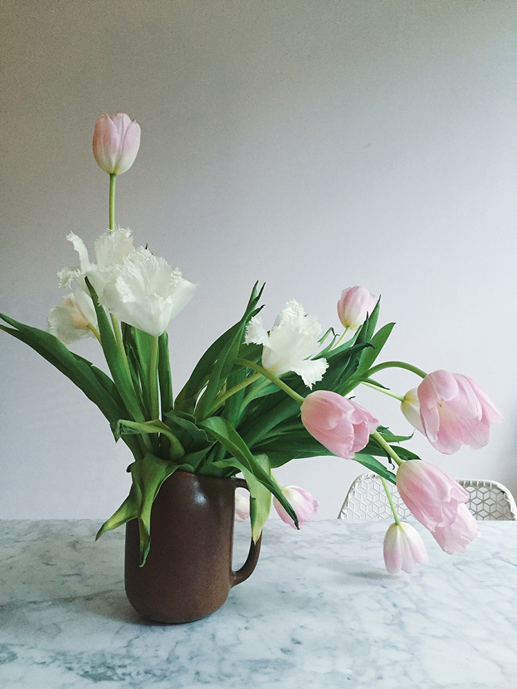 frilly white and pink tulips, the perfect spring bouquet in a simple brown earthenware pitcher