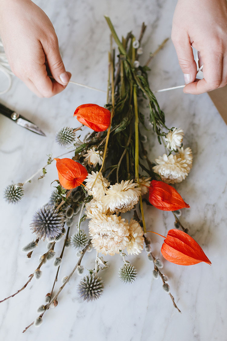 Click thru to learn how I used dried flowers, mini twinkly lights, and white pumpkins for a super simple, eye-catching centerpiece for fall or Thanksgiving entertaining. Get the full DIY tutorial on Jojotastic.com just in time for the holidays and all those dinner parties!