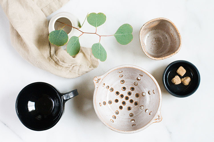 handmade ceramics from Seattle. navy blue glaze earthenware with speckled white interior. black porcelain pinch bowls. artisan made colander and berry bowl.