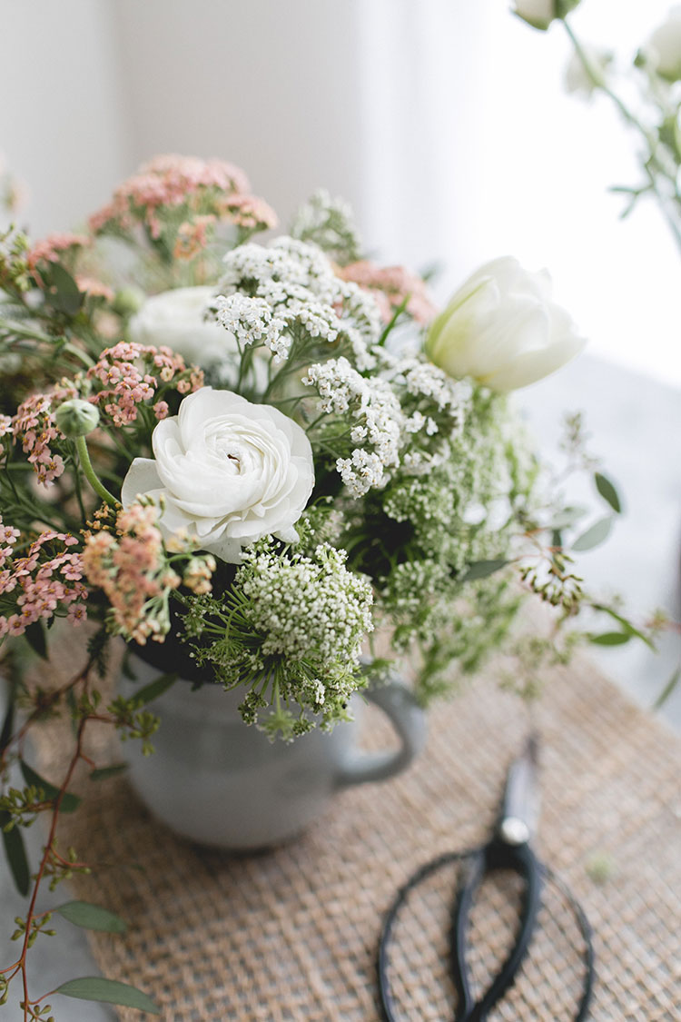 learn how to make this gorgeous springtime centerpiece for entertaining. The DIY arrangement includes Cottage Yarrow, Ranunculus, Seeded Eucalyptis, Queen Anne's Lace, Tulips. Get the full tutorial on jojotastic.com