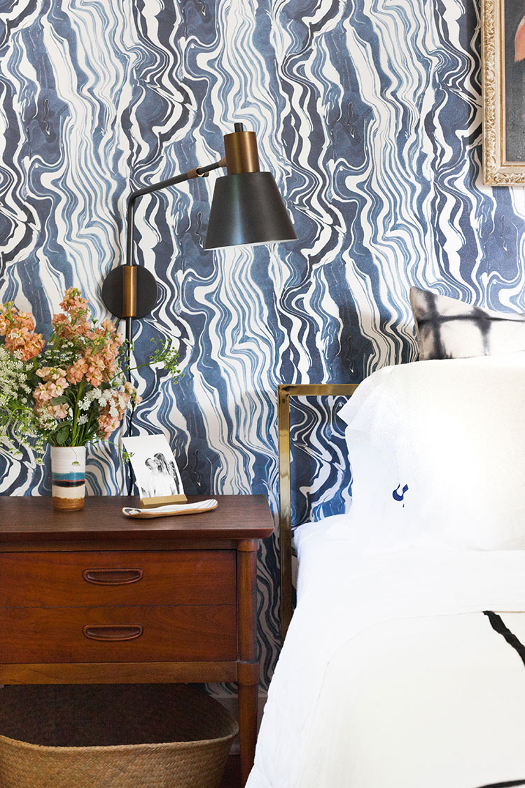 It's reveal day for my bedroom makeover and renovation! Design details include navy blue marbled wallpaper, vintage lady painting, gold bed, mid-century modern vintage furniture, vintage Turkish rug, @Rejuvenationinc lighting and sconces, @allmodern lamb fur and kilim pillows, and a great small space solution for a room without a closet! Get the entire source list on Jojotastic.com