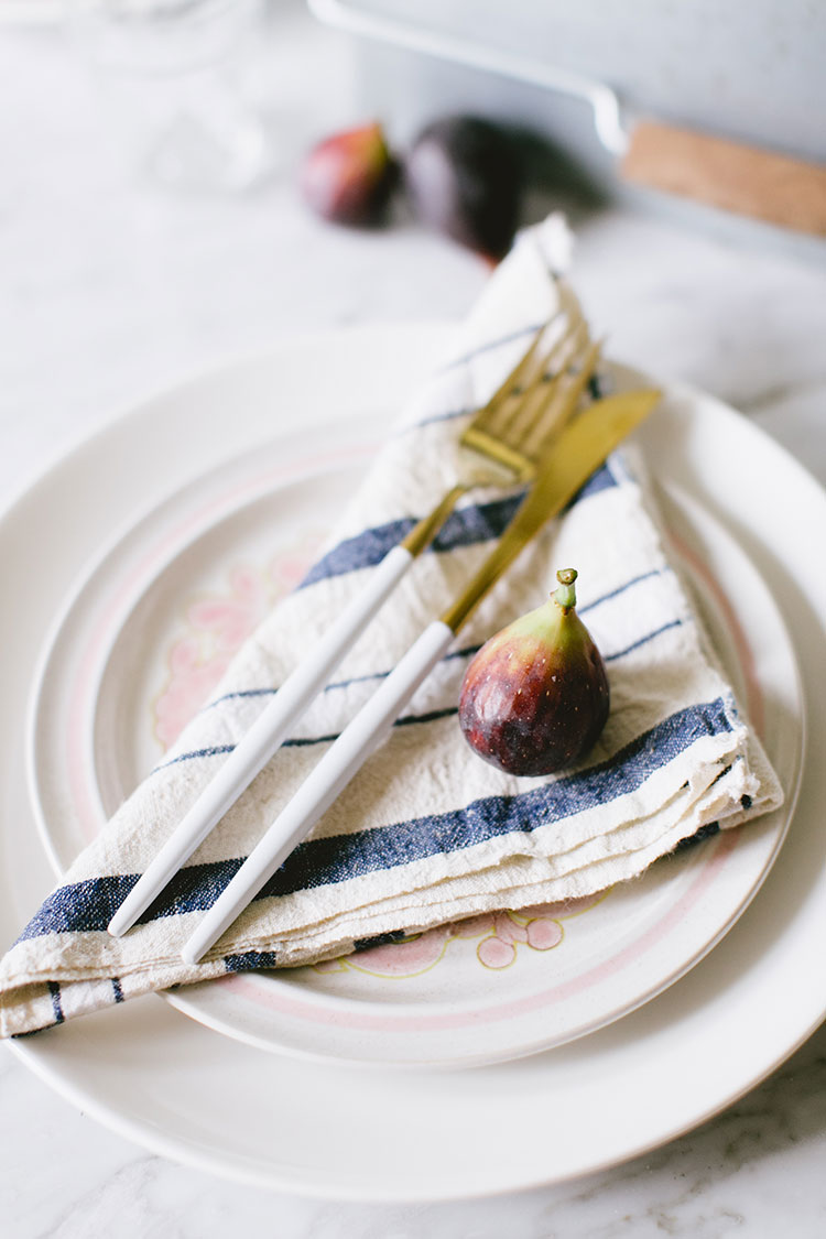 small space entertaining tips and inspiration. a rustic tablescape to celebrate summer with vintage floral plates, modern white cutlery, vintage linen napkins, and simple glassware. via @jojotastic
