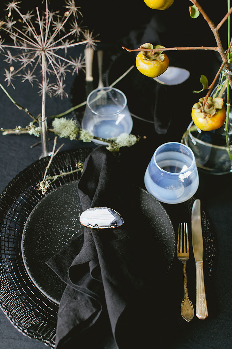 Dramatic and sophisticated all black Halloween tablescape. Inspiration for small space entertaining via jojotastic.com with black plates, placemats, geode napkin rings, milky glass, and vintage silver flatware.