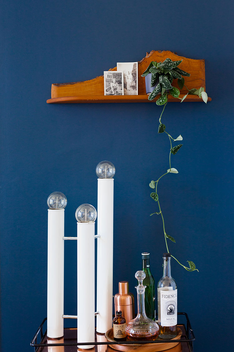 the Domino Design Blog Awards + a lot of emotions. dark navy blue wall with live edge shelf and vintage lighting and bar cart.