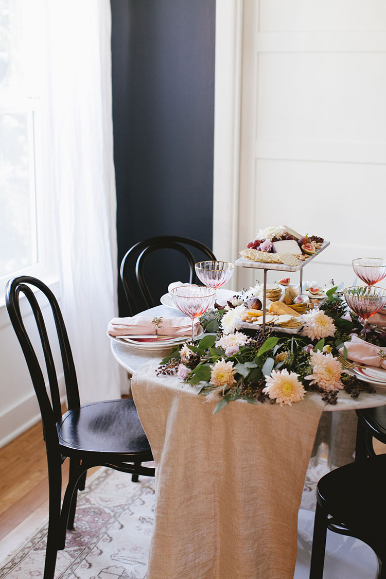 a whimsical blush Thanksgiving tablescape. Inspiration for small space entertaining via jojotastic.com with pink swirled canape plates, pink and gold wine glasses, modern white and gold utensils, pink and natural linens, and thankful napkin rings. #entertaining #thanksgiving