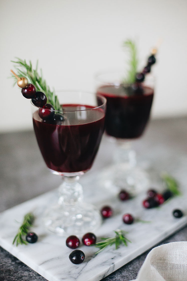 a festive amaro manhattan cocktail recipe perfect for entertaining holiday guests. made with amaro, bourbon, cranberry juice, orange bitters, and rosemary. Get the full recipe on jojotastic.com #holidayrecipe #christmascocktail #christmasrecipe