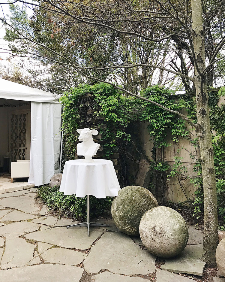 overgrown garden with statuary and orbs. goat head bust, whimsical landscaping.