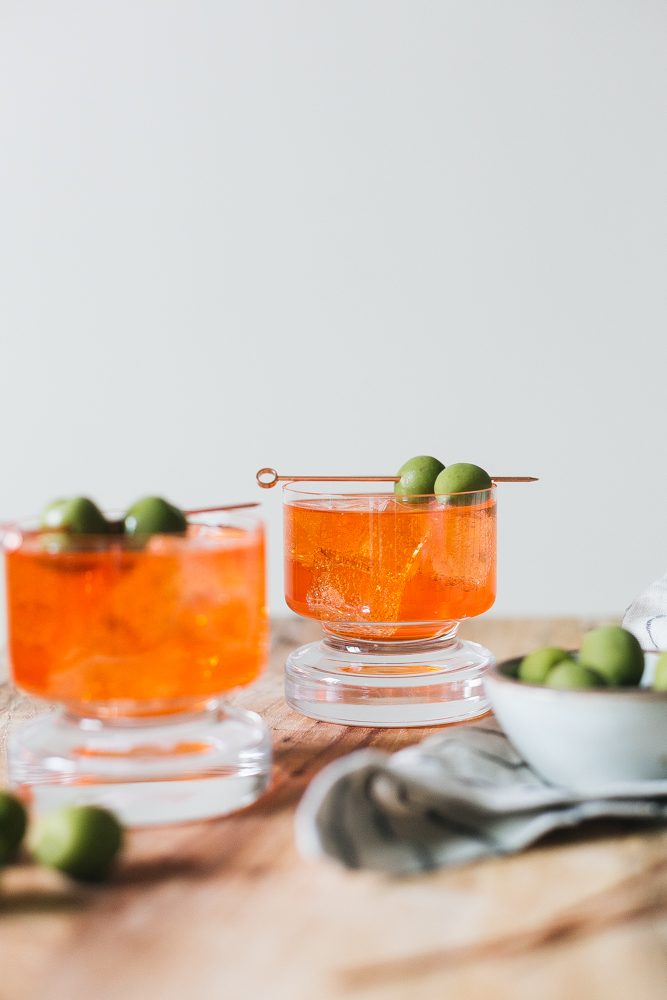 Our Twist on the Classic Negroni Recipe made with Aperol, Gin, Vermouth, Celery Bitters, and Grapefruit Bitters. Aperol Negroni aperitivo, Italian cocktail recipe. #italy #italiancocktail #aperitivo #campari  #negroni #aperolnegroni