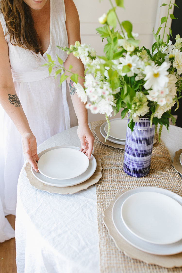 Summer-Inspired Brunch Tablescape with layered white plates, wooden chargers, raw rough linen, vintage flatware utensils, and gold rimmed glasses. #tablescape #tabletop #entertaining #smallspaces #hostess