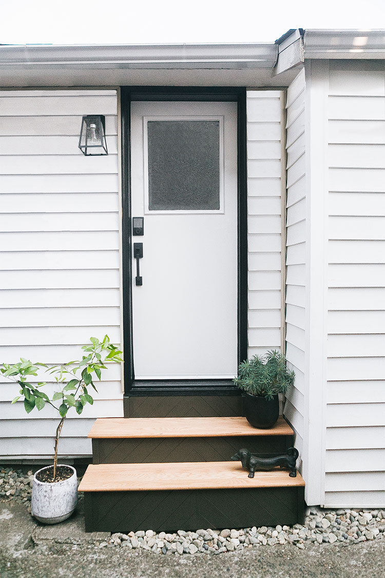 Our Backdoor Mini Makeover with @schlagelocks including DIY herringbone stairs with black stain, new door hardware, new modern farmhouse outdoor wall sconce. Minimalist modern shiplap on stair risers. #SchlageCustom #ad