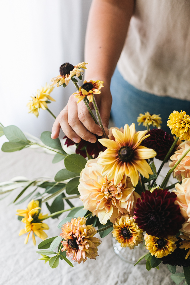 An Early Fall Centerpiece of Peach and Burgundy Flowers DIY from Jojotastic. Floral arrangement with dahlias, Rudbeckia. Baptisia Foliage, and Olive Foliage. #DIY #flowerarrangement #florals #floral #floralarrangement #floraldiy #fallflowers #dahlias #centerpiece