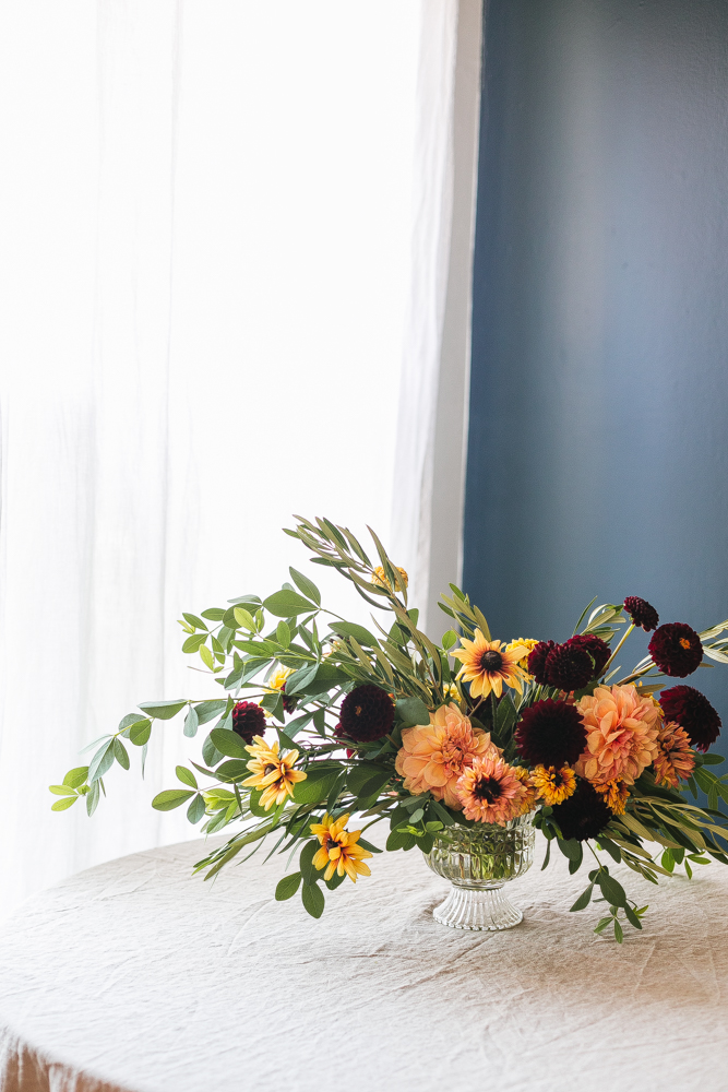 An Early Fall Centerpiece of Peach and Burgundy Flowers DIY from Jojotastic. Floral arrangement with dahlias, Rudbeckia. Baptisia Foliage, and Olive Foliage. #DIY #flowerarrangement #florals #floral #floralarrangement  #fallflowers #dahlias #centerpiece