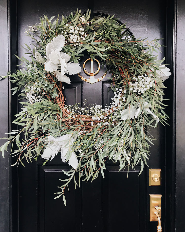 Holiday Hosting Tips When You Live Small. organic eucalyptus and grapevine wreath with baby's breath. brass anchor door knocker, glossy black front door, brass hardware. #holidays #hosting #hostess #hostesstips #smallspaces #tinyhouse #entertaining #christmas