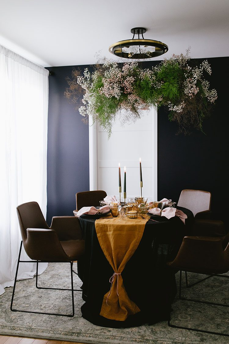 How to Style a Moody Fall-Inspired Dinner Party in a Small Space. A fall tablescape with mini cloches, gold taper holders, candlesticks, black dinner plates, smoke glass, mercury glass. #entertaining #tipsandtricks #fall #tablescape #thanksgiving #halloween #smallspaces #dinnerparty