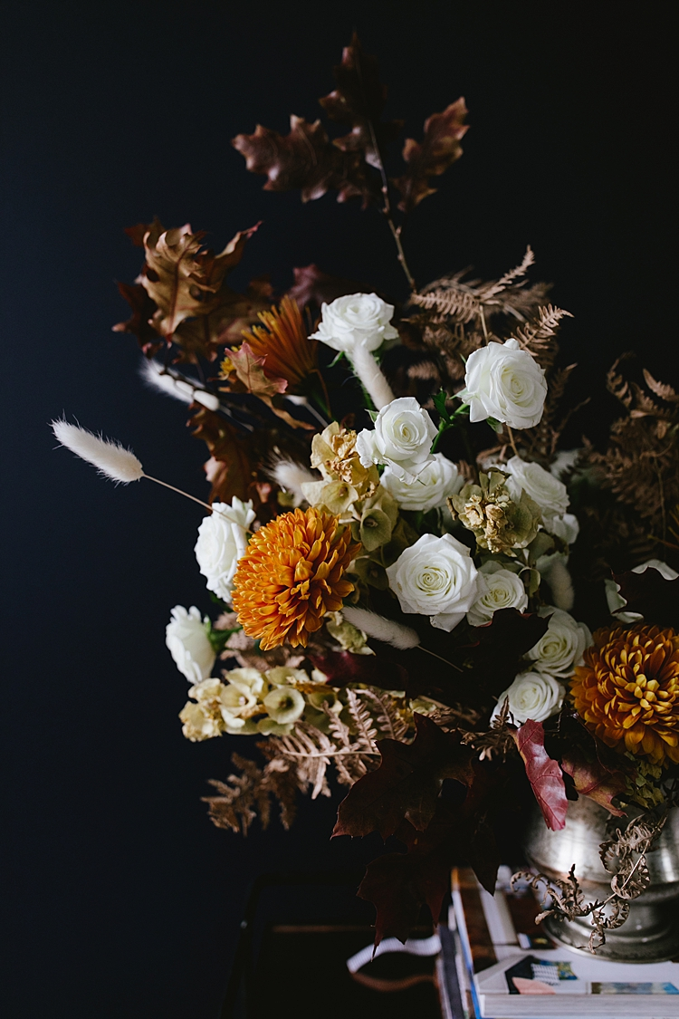 Learn How to Make this Modern Thanksgiving Centerpiece with Dried Flowers, Golden Chrysanthemums, Cream Spray Roses, Branches of oak and maple leaves. Get the full DIY tutorial on Jojotastic.com #flowerarrangement #floralarrangement #flowerarranging #centerpiece #thanksgiving #fall #thanksgivingdecor #florals #flowers #fallflowers #friendsgiving