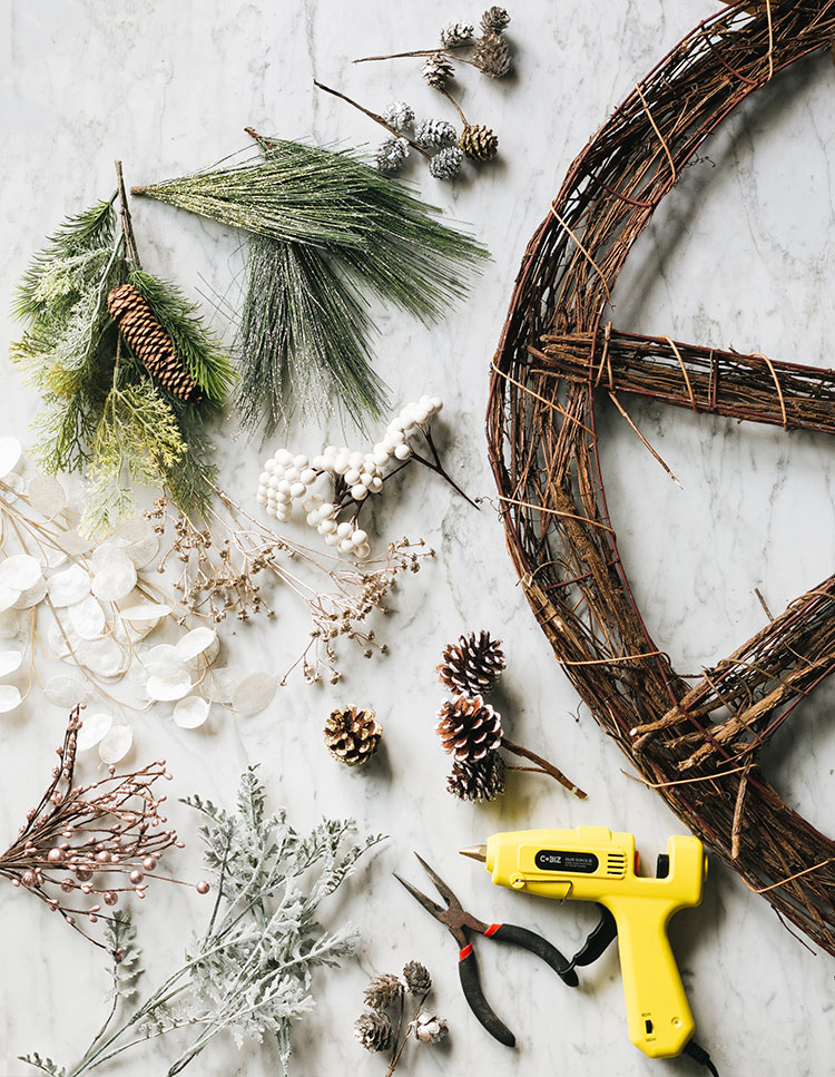Peace Sign Wreath with Faux Foliage DIY. Put a modern twist on a classic grapevine wreath with faux flowers. It's the perfect large wreath to hang outdoors all winter long. #peacesign #wreath #diywreath #christmas #diy #holidays #christmasDIY #holidayDIY #grapevinewreath #fakeflowers #fauxflowers