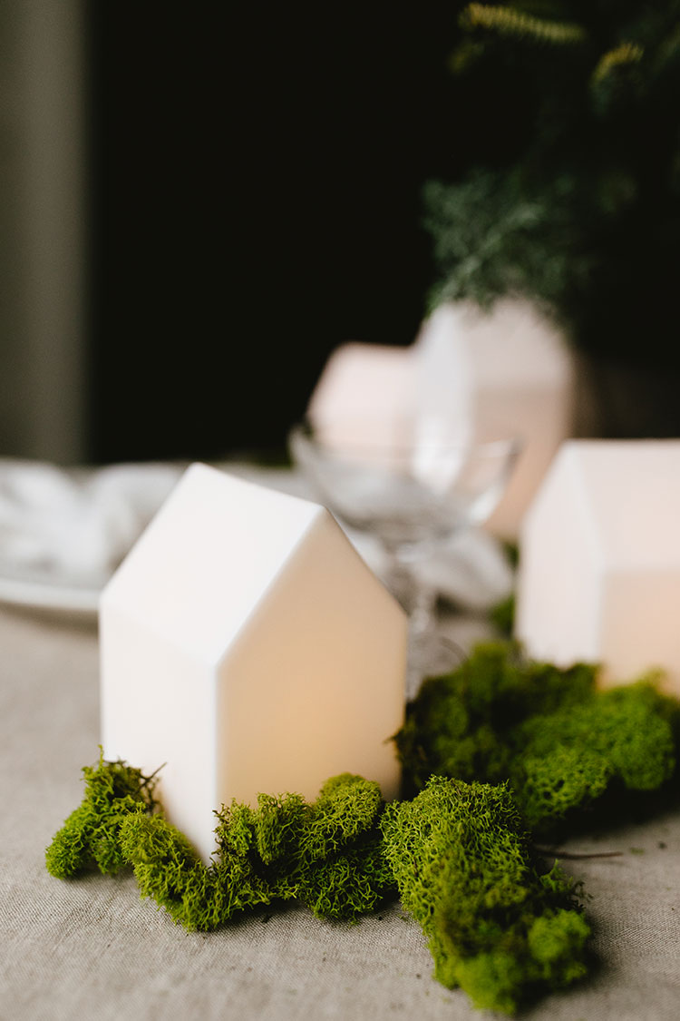 How to Make a Foraged Evergreen Centerpiece for Your Winter Tablescape! DIY tutorial for  a flower arrangement for a Festive Forest Christmas Tablescape, inspired by Nordic and Scandinavian decor and hygge holiday decorations. #christmastable #tablescape #holidaytable #christmasdecor #holidaydecor #greendiningtable #diningtable #christmasvillage #hygge #greenery #pine #greencenterpiece #centerpiece