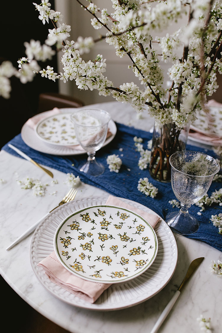 Style a simple spring tablescape with these 5 easy-to-follow tips from a professional prop stylist — perfect for Easter, Mother's Day, or a weekend brunch! Plum branches centerpiece, layered patterned plates, touches of gold. Small space entertaining tips. #entertaining #tablescape #spring #springtime #mothersday #easter #centerpiece #plumblossoms