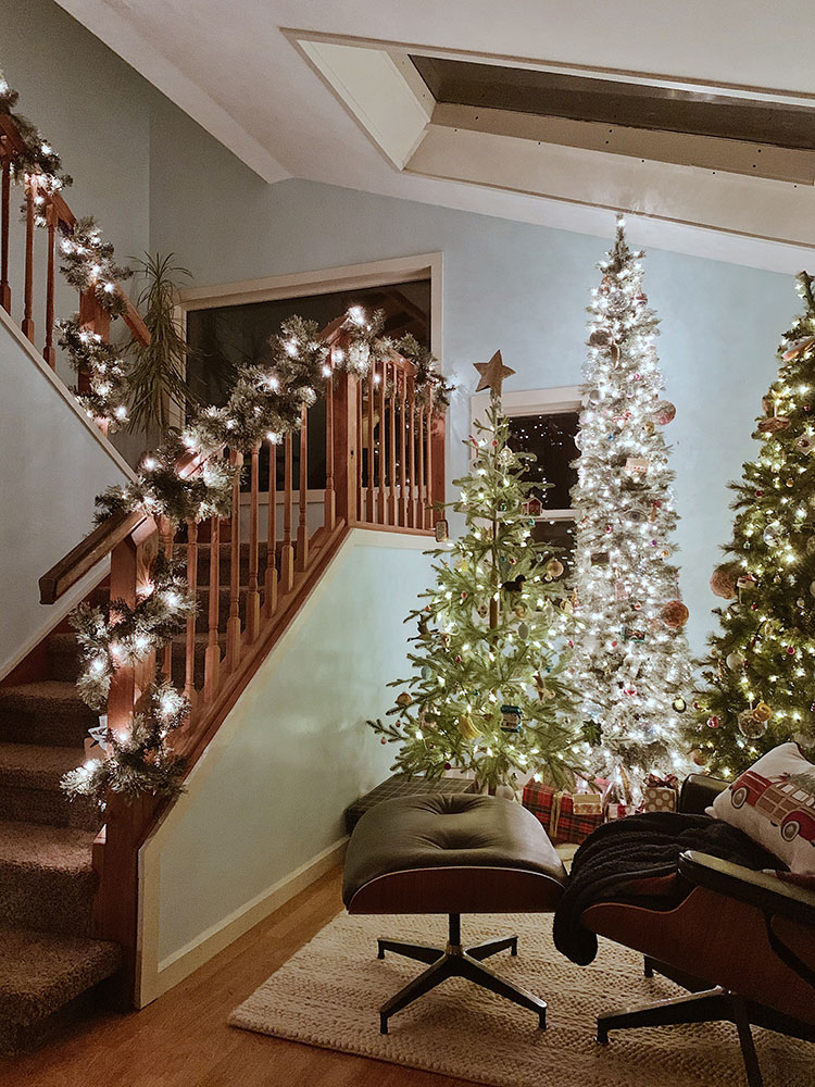 indoor christmas tree forest and lit garlands on banister in a PNW cabin