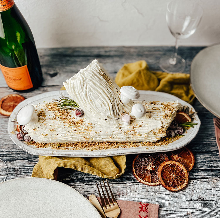 Orange Spice Bûche de Noël (Yule Log Recipe) with meringue mushrooms, swiss buttercream, candied cranberries, candied rosemary and more! a fancy and traditional holiday dessert recipe