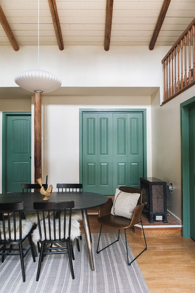 Before/After Makeover Reveal: Our Eclectic Scandinavian Inspired Cabin Dining Room. Pill shaped dining table from Allmodern, George Nelson saucer bubble pendant light, black farmhouse dining chairs, cognac leather upholstered dining chairs, green doors, cedar wood timbers